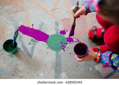 A child holding a glass with paint and a paintbrush, playfully painting abstract things on a floor with pink and teal color