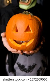 Child holding Hallowe'en pumpkin with a carved face