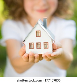Child holding house in hands outdoors