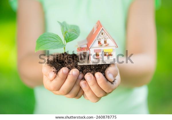 Kinderhaus und Baum in Händen auf grünem Frühlingshintergrund. Immobilienkonzept