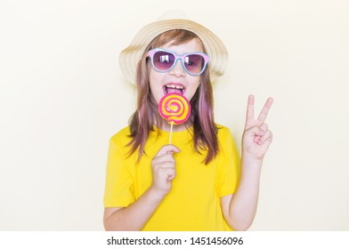 The child is holding a lollipop. Childish joy is sweetness. Little girl in a yellow T-shirt and glasses.