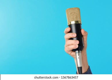 Child holding microphone on color background, closeup of hand. Space for text
