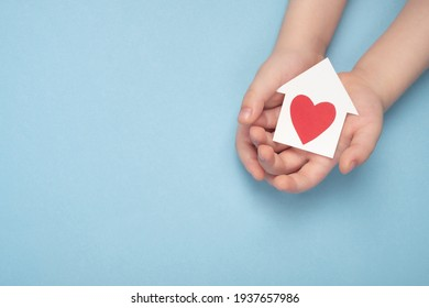 Child holding miniature house with little heart on light blue background. Care, health insurance, adoption, world heart day and healthcare concept. Top view, copy space