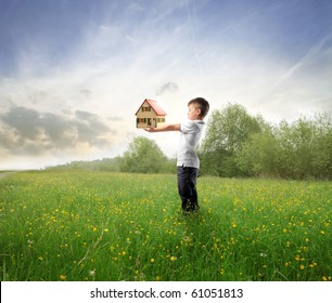 Child holding the model of a house on a green meadow
