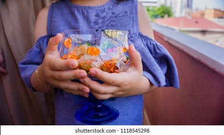 The child holding and offering or presenting a cup of traditional Turkish sugars in Ramadan / Sugar / Sacrifice Feast or Holiday. Religious Feast of Muslims. Eid Mubarak. Eid al-Adha. Feast concept.