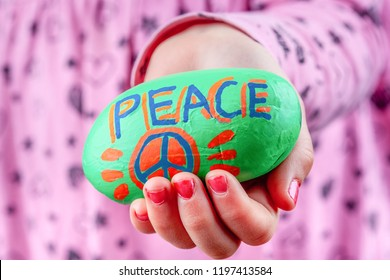 Child holding painted rock wit PEACE lettering and symbol. Focus on foreground