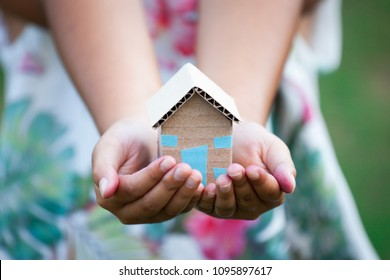 Child holding paper house in hands as real estate and family home concept