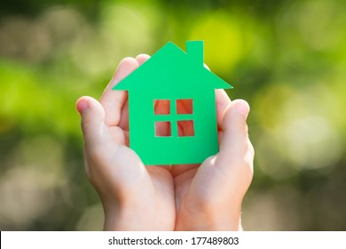 Child holding paper house in hands against spring green background