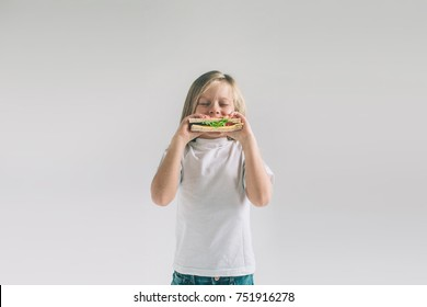 Child holding a piece of hamburger. Kid eats fast food. not helpful food. very hungry baby. Girl isolated on white background