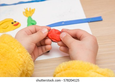 The child is holding a piece of red clay, close-up