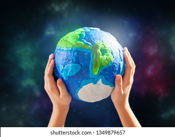 Child holding planet in hands against space background. Earth day holiday concept.
