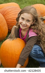Child Holding a Pumpkin In A Patch On a Farm