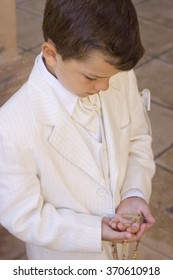 Child holding a rosary with a crucifix during his first communion celebration