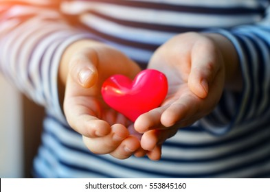 child holding a small pink heart. symbol of love, family, hope. Backgrounds for cards on Valentine's Day. Backgrounds for social posters about the preservation of the family and children.