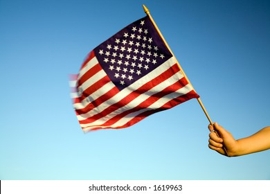 Child holding small US flag on the wind outdoor.