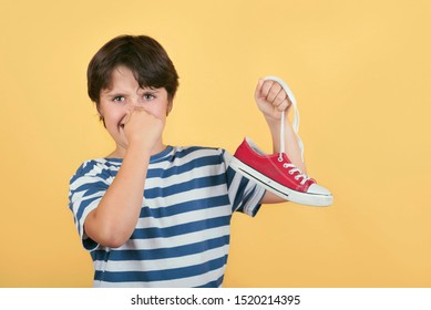 Child holding smelly sneakers shoes on yellow background