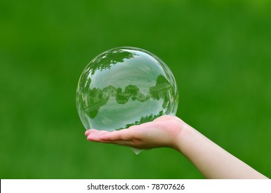 Child holding soap bubble with house reflection
