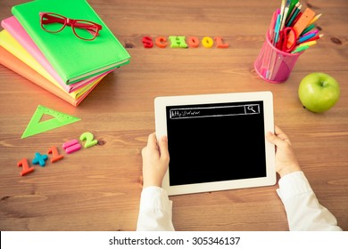 Child holding tablet PC in hands. School items on wooden desk in class. Education concept. Top view