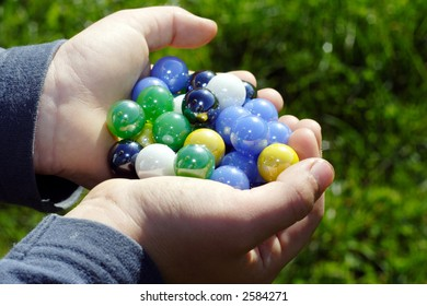 Child holding two hands full of marbles outdoors in the sunshine against a green grassy background