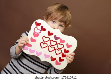 Child holding  Valentine's Day Craft with Heart stickers
