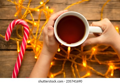 Child holding warm tea in the christmas cup