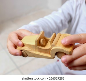 Child holding wooden car
