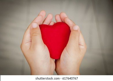 Child holds a big red heart in his hands. Sincerity, sincere love stock image. Give-away, charity, family volunteering, philanthropy, love concept.