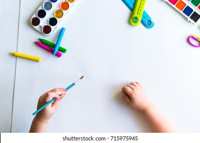 The child holds the brush over a blank sheet of white paper and ready to paint with watercolors