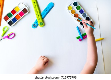 The child holds the brush over the palette and ready to paint on a blank sheet of white paper with watercolors