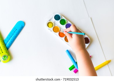 The child holds the brush over the palette and ready to paint on a blank sheet of white paper with watercolors. Blurred