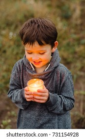 A child holds a burning candle in his hand