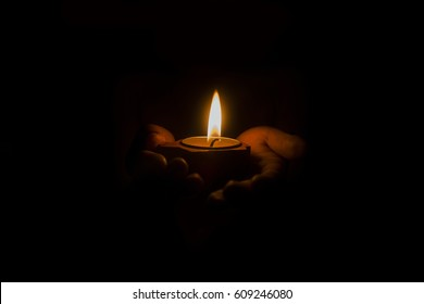 a child holds a candle in hands,focus on candle at dark background