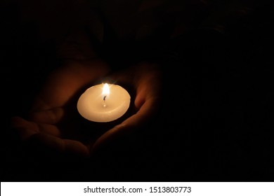 The child holds a candle in his hands in a dark room.