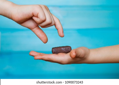 The child holds a chocolate candy in the palm of his hand, sharing it with his friend