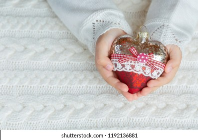 Child holds a glass heart, a Christmas toy in the hands on the background of a warm knitted sweater