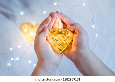 The child holds a golden heart in his hands, a Christmas tree decoration - a garland in his hands against the background of white tulle and bokeh.