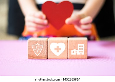 A child holds a heart in the background. Wood block stacking with icon healthcare medical, insurance for your health concept.