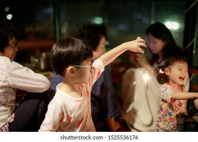 Child holds in his hands a Sparkler on a dark background