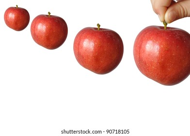 A child holds a large red apple fruit stem and wants to put him last among the other three, in isolation