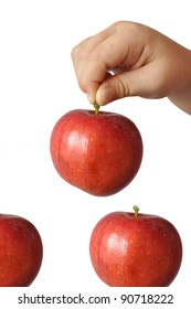 A child holds a large red apple fruit stem and wants to put it on top of two others, isolation