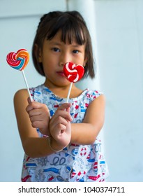child holds the lollipop in the form of heart
