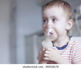 child holds a mask vapor inhaler. treatment of asthma. breathing through a steam nebulizer. concept of inhalation therapy apparatus. copy space for your text