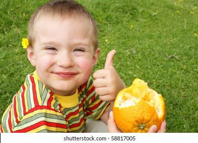 The child holds orange ,background grass