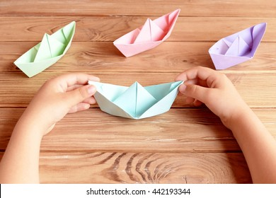 Child holds the origami ship in his hands. Colorful ships origami paper folding on a wooden table. Preschool and kindergarten paper crafts. Summer project idea