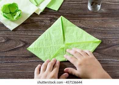 The child holds a paper square and fold it corner. The child makes crafts out of paper lily. Paper napkins on a wooden table. Children's art project, a craft for children.