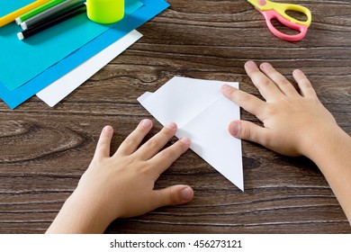 The child holds a paper strip square and fold him in half. The child makes crafts out of paper boat. Glue, paper, scissors on a wooden table. Children's art project, a craft for children.