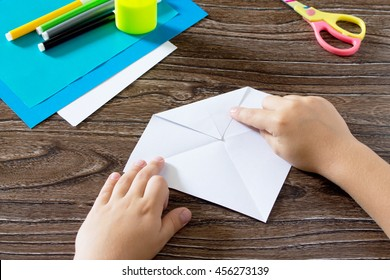 The child holds a paper strip square and fold it corner. The child makes crafts out of paper boat. Glue, paper, scissors on a wooden table. Children's art project, a craft for children.