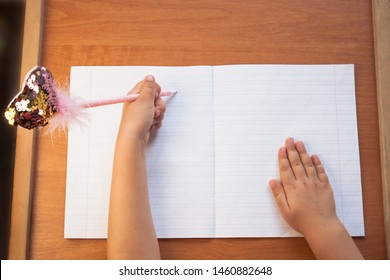 A child holds a pen in his left hand and writes in an empty notebook on a wooden desk. Back to school concept. Top view, copy space.