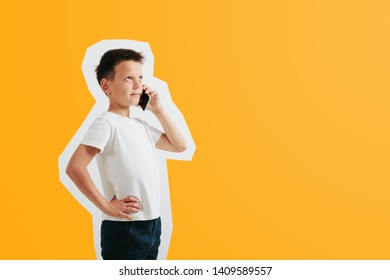The child holds the phone in his hand on a orange background. Color