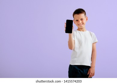 The child holds the phone in his hand on a Violet background. Color
